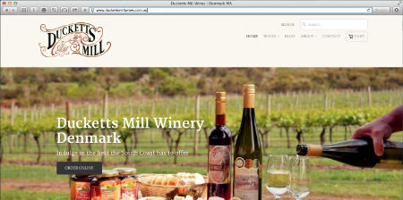 A screenshot of the home page of Ducketts Mill Winery website showing wines and cheeses on a platter in a vineyard.
