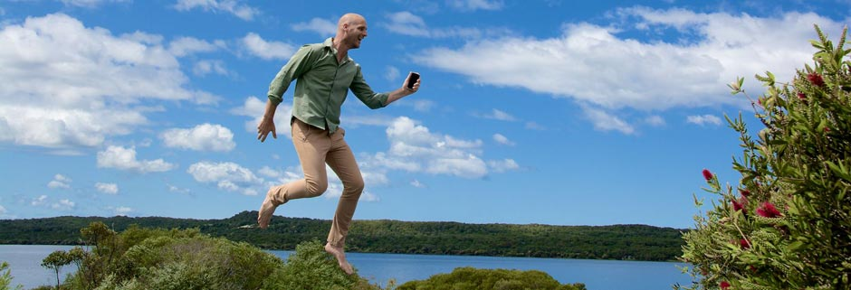 Man jumping in the air holding a mobile phone